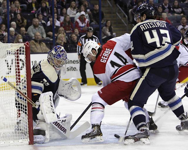 Columbus Blue Jackets' Sergei Bobrovsky, left, of Russia, makes a save as teammate Artem Anisimov, right, also of Russia, and Carolina Hurricanes' Nathan Gerbe fight for a rebound during the first period of an NHL hockey game on Friday, Jan. 10, 2014, in Columbus, Ohio. (AP Photo/Jay LaPrete)