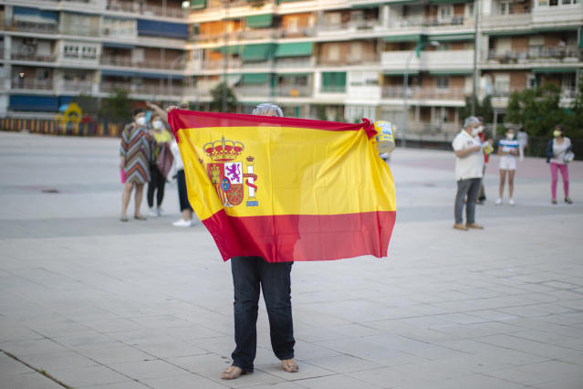 A woman holds a Spanish flag during a protest against the Spanish government amid the lockdown to prevent the spread of coronavirus in Alcorcon, Spain, Friday, May 22, 2020. The Spanish government is allowing Madrid and Barcelona to ease their lockdown measures, which were introduced to fight the coronavirus pandemic. (AP Photo/Manu Fernandez)