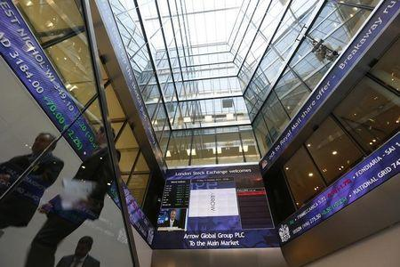 People pass electronic information boards at the London Stock Exchange in the City of London