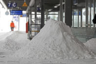 A Deutsche Bahn employee clears snow on a platform at the main station in Magdeburg, Germany, Sunday, Feb. 7, 2021. (Peter Gercke/dpa via AP)