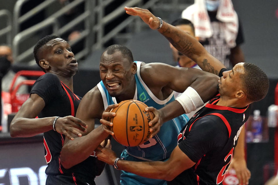 Charlotte Hornets center Bismack Biyombo (8) gets between Toronto Raptors forward Chris Boucher (25) and guard Norman Powell (24) during the second half of an NBA basketball game Saturday, Jan. 16, 2021, in Tampa, Fla. (AP Photo/Chris O'Meara)
