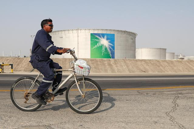 A worker rides a bicycle by oil tanks at an oil processing facility of Saudi Aramco, a Saudi Arabian state-owned oil and gas company, at the Abqaiq oil field. (Stanislav Krasilnikov\TASS via Getty Images)