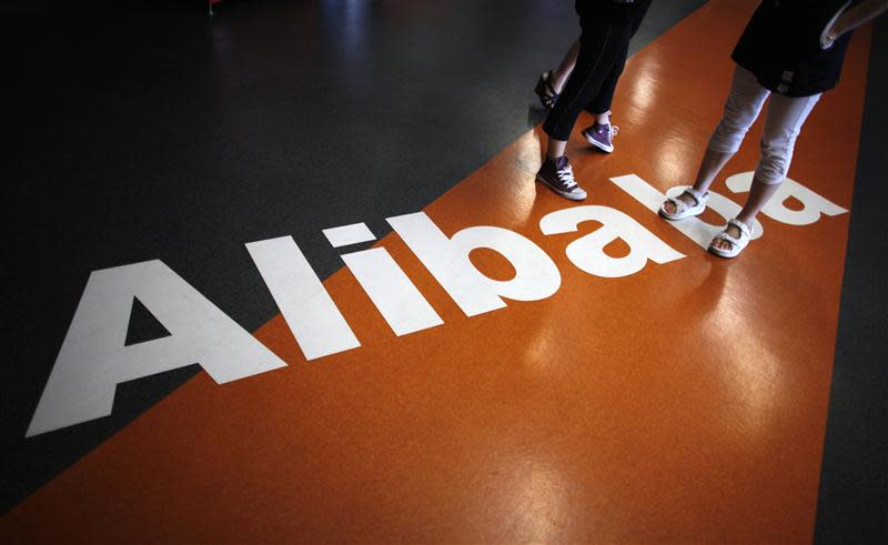 File of employees standing on a logo of Alibaba (China) Technology Co. Ltd during a media tour organised by government officials at its headquarters on the outskirts of Hangzhou