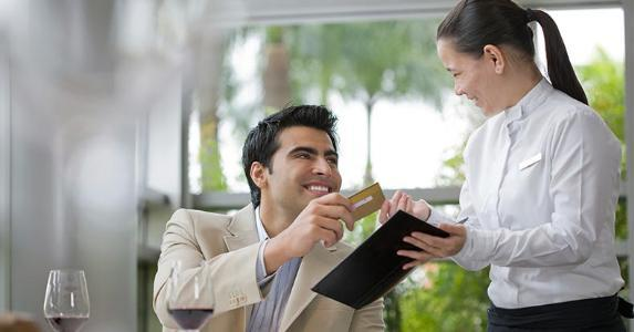 Man handing his credit card to waitress | AAGAMIA/Getty Images