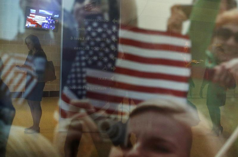 Campaign worker Erin Callahan from New York, left, is seen through the store windows texting on her phone at the Republican National Convention in Tampa, Fla., on Monday, Aug. 27, 2012. (AP Photo/Jae C. Hong)
