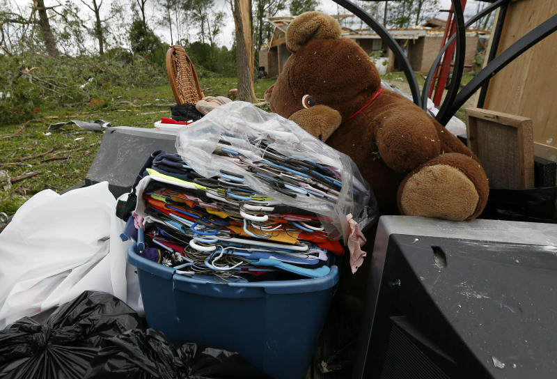 A Morton, Miss., resident loads all salvageable items on a trailer for removal from her storm damaged house, Friday, April 19, 2019. Strong storms again roared across the South on Thursday, topping trees and leaving a variety of damage in Mississippi, Louisiana and Texas. (AP Photo/Rogelio V. Solis)