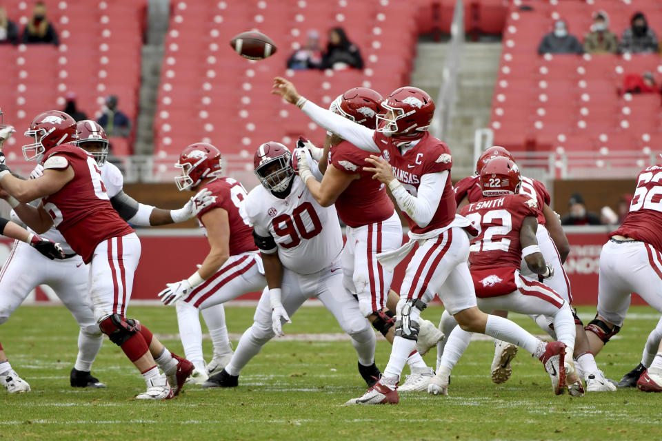 FILE - In this Dec. 12, 2020, file photo, Arkansas quarterback Feleipe Franks (13) throws a pass as Alabama defensive lineman Stephon Wynn Jr. (90) puts on the pressure during the second half of an NCAA college football game in Fayetteville, Ark., with few people in the stands. Southeastern Conference football is trying to get back to normal, with filled-up stadiums and fired-up grills outside. The SEC will fully reopen for business this weekend, with 11 of the 14 teams hosting games after a season of shrunken crowds and no on-campus tailgating in states where fall Saturdays are all about college football. (AP Photo/Michael Woods, File)