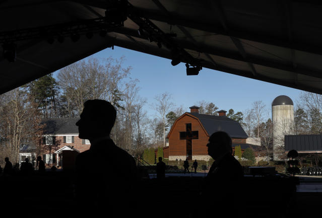 <p>The Billy Graham Library is seen in the background as people are silhouetted as they arrive for the funeral service for the late U.S. evangelist Billy Graham in Charlotte, N.C., March 2, 2018. (Photo: Leah Millis/Reuters) </p>