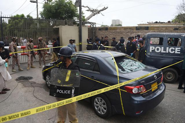 EDITORS NOTE: Graphic content / Policemen guard a car used by alleged gunmen outside the Pakistan Stock Exchange building in Karachi on June 29, 2020. - At least six people were killed when gunmen attacked the Pakistan Stock Exchange in Karachi on June 29, with a policeman among the dead after the assailants opened fire and hurled a grenade at the trading floor, police said. (Photo by Rizwan TABASSUM / AFP) (Photo by RIZWAN TABASSUM/AFP via Getty Images)
