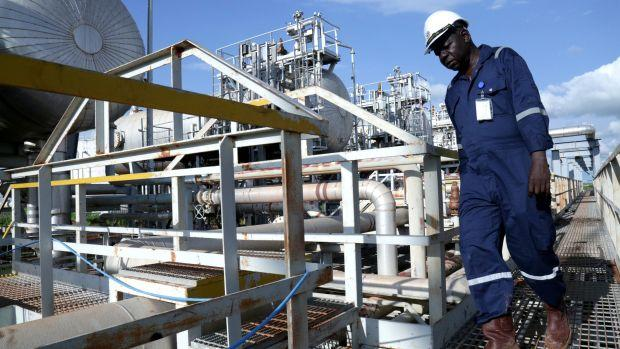 A worker walks by an oil well at the Toma South oil field to Heglig, in Ruweng State