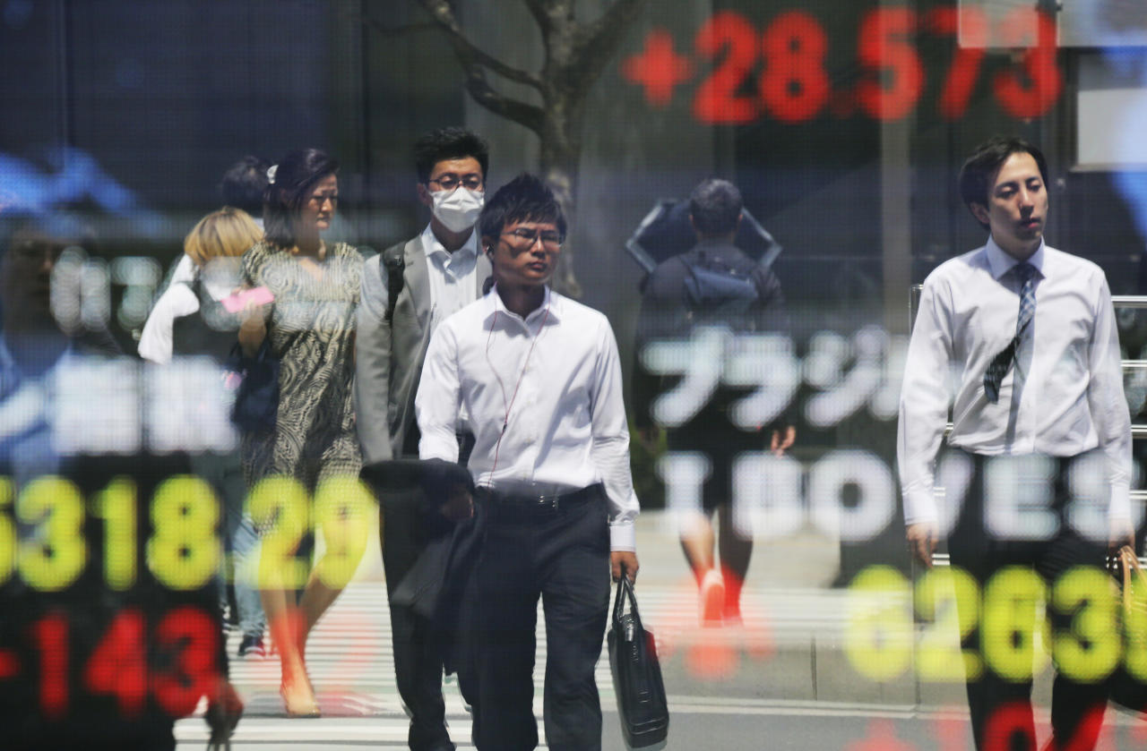 People are reflected on the electronic board of a securities firm in Tokyo, Monday, May 22, 2017. Asian stocks rose Monday, cheered by the latest rally on Wall Street and relative quiet in U.S. politics as President Donald Trump began his first official trip overseas as president. (AP Photo/Koji Sasahara)