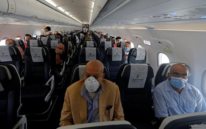 As the world begins to cautiously open its borders once more, travellers wear protective face masks on a plane in Cairo, Egypt - Reuters