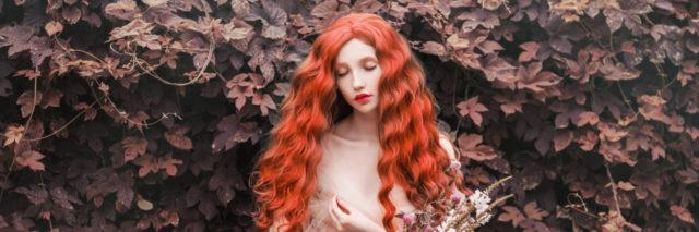 Woman with curly red hair with a tulle dress in a garden, holding flowers.