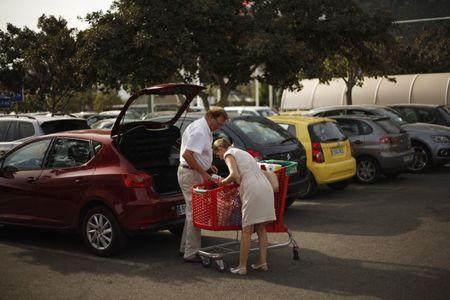 A couple unload grocery into their car after shopping at a supermarket at La Canada shopping centre in Marbella