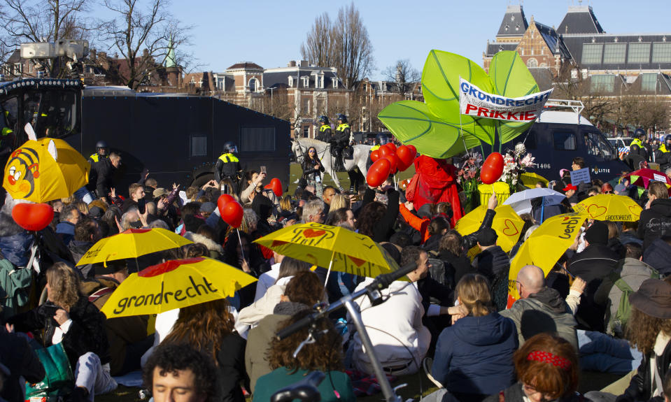 Dutch riot police enclose a group of demonstrators who refused to leave after police broke up a demonstration of hundreds of people who protested against the coronavirus lockdown and curfew on Museum Square in Amsterdam, Netherlands, Sunday, Feb. 28, 2021. The group was eventually allowed to leave. (AP Photo/Peter Dejong)