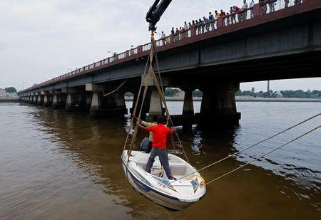 Rescue workers lift a boat with the help of a crane at the Sabarmati river after a flood alert in Ahmedabad, India, August 22, 2016. REUTERS/Amit Dave