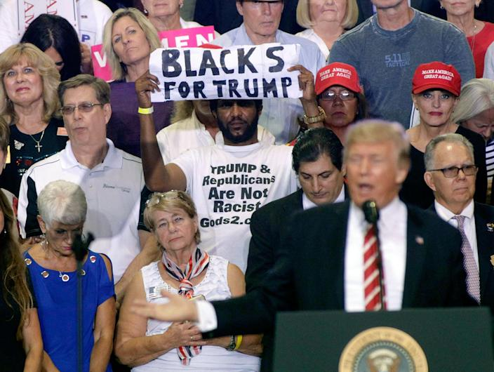 A controversial supporter of President Trump holds up a sign as the president speaks to a crowd at the Phoenix Convention Center Aug.22, 2017. (Photo: Ralph Freso/Getty Images)