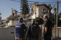 People look at a house after it was hit by a rocket fired from the Gaza Strip, in Yehud, central Israel, Wednesday, May 12, 2021. The house was hit Tuesday as barrage of rockets fired from the Gaza Strip toward central Israel. (AP Photo/Heidi Levine)