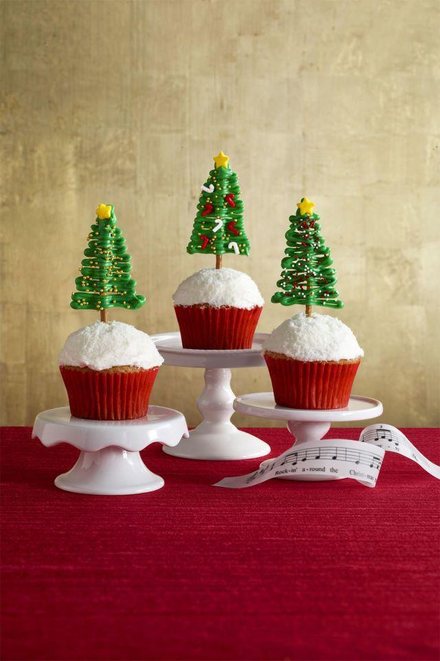 """<p>Use festive sprinkles to decorate these adorable mini trees and cupcakes. <br></p><p><strong><a href=""""https://www.womansday.com/food-recipes/recipes/a56903/rockin-around-the-christmas-tree-cupcakes-recipe/"""" rel=""""nofollow noopener"""" target=""""_blank"""" data-ylk=""""slk:Get the recipe."""" class=""""link rapid-noclick-resp"""">Get the recipe.</a></strong></p>"""