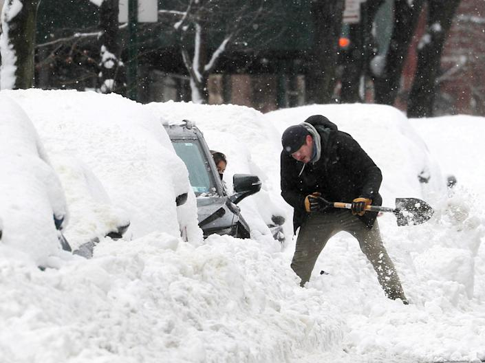 <p>A man helps a driver dig her car out from deep snow on Manhattan's upper west side after a winter storm in New York City, New York, US, 2 February, 2021</p> (REUTERS)