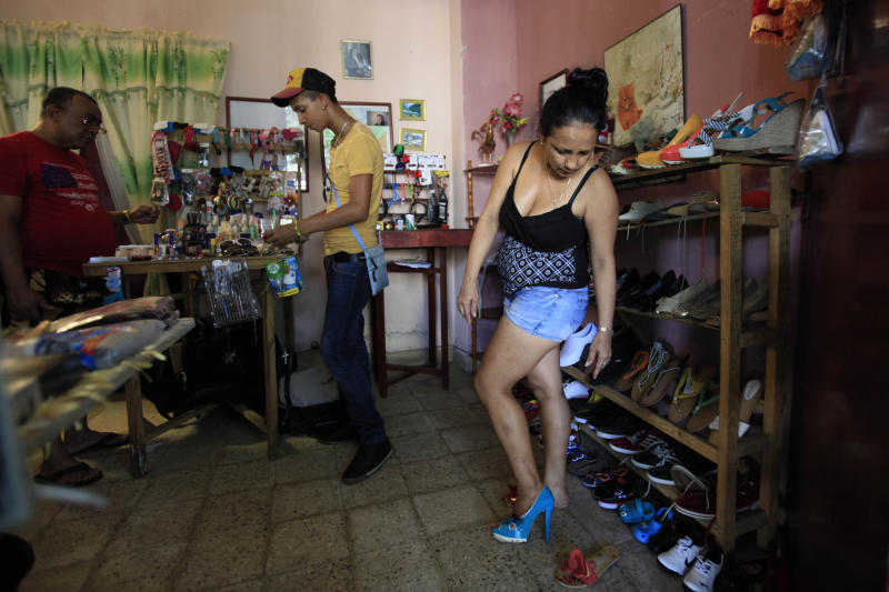 In this Oct 11, 2013 photo, a woman tries on a shoe inside the home of a small business owner in Havana, Cuba. Three months from now, authorities will begin enforcing a new law banning the private sale of imported goods. For entrepreneurs who have carved out modestly successful livelihoods after investing their life savings to launch import-dependent businesses, the new measure feels like a big step back. (AP Photo/Franklin Reyes)