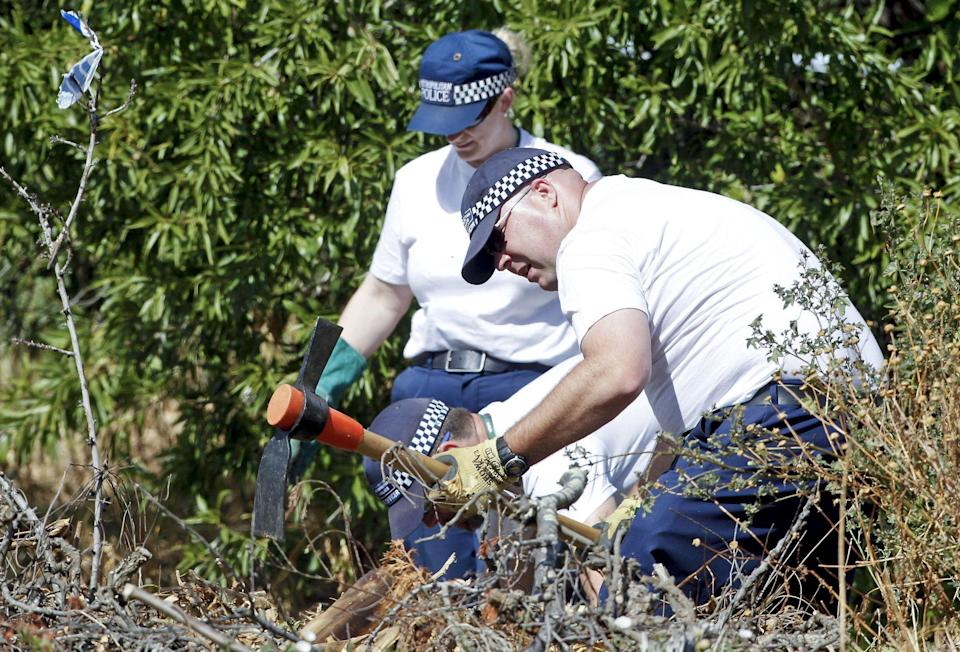 Police search bushes for traces of the missing girl in Portugal in June 2014. (Rex)