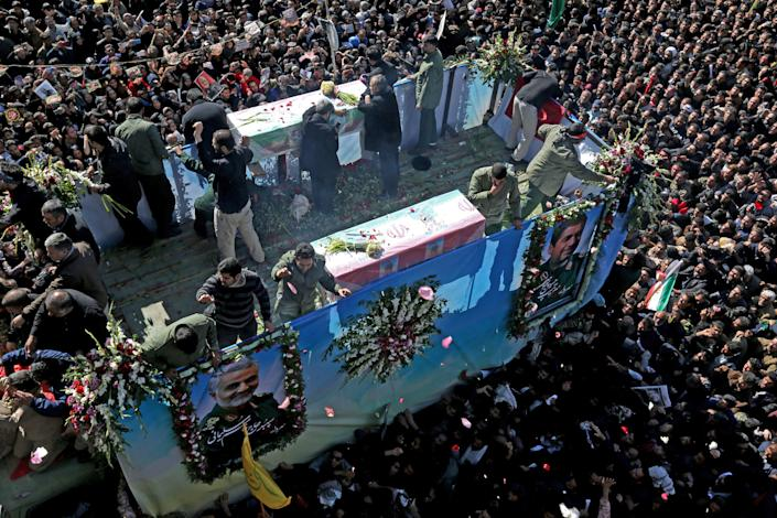 "Iranian mourners gather around a vehicle carrying the coffin of slain top general Qasem Soleimani during the final stage of funeral processions, in his hometown Kerman on January 7, 2020. - Soleimani was killed outside Baghdad airport Friday in a drone strike ordered by US President Donald Trump, ratcheting up tensions with arch-enemy Iran which has vowed ""severe revenge"". The assassination of the 62-year-old heightened international concern about a new war in the volatile, oil-rich Middle East and rattled financial markets. (Photo by ATTA KENARE / AFP) (Photo by ATTA KENARE/AFP via Getty Images)"