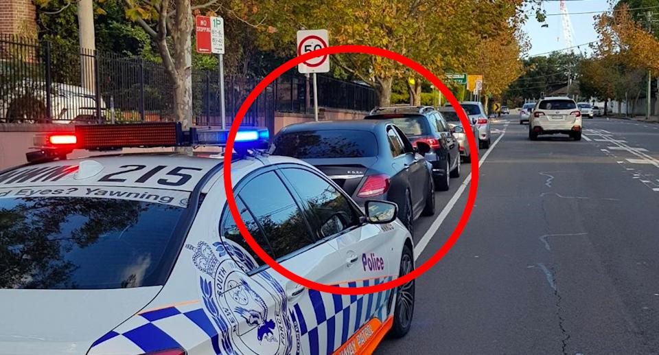 A Mercedes AMG E63S circled in front of a NSW Police car.