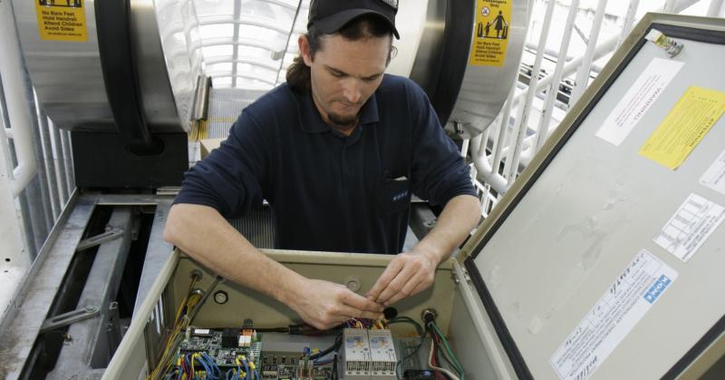 A repairman working on a controller box for an elevator.