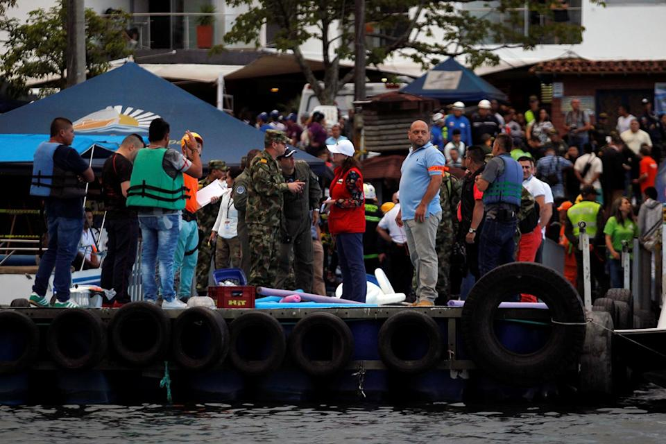 <p>Rescuers wait at the dock after a tourist boat sank with 150 passengers in the Guatape reservoir, Colombia, June 25, 2017. (Fredy Builes/Reuters) </p>