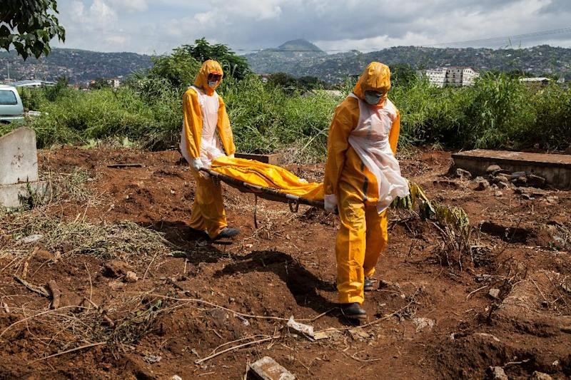 A team of funeral agents specialised in the burial of victims of the Ebola virus carry a body prior to put it in a grave at the Fing Tom cemetery in Freetown, on October 10, 2014