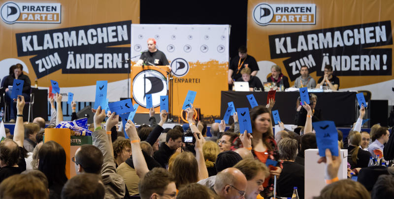 """Members of the Pirates party vote during their party convention in Neumuenster, northern Germany, Saturday, April 28, 2012. Pirates are capturing Germany's political system: The party started as a marginal club of computer nerds and hackers, but its appeal as an anti-establishment movement has lured many young voters to the ballot boxes, gaining it parliamentary seats in two consecutive state elections. Slogans in the background left and right read: """"Get Reay for Changing"""". (AP Photo/dapd, Clemens Bilan)"""