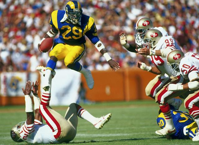 "Hall of Fame running back Eric Dickerson (29), who played for the Rams for four-plus seasons in the 1980s, goes airborne to avoid the San Francisco 49ers defense in a game at Anaheim Stadium. <span class=""copyright"">(Peter Brouillet / Getty Images)</span>"