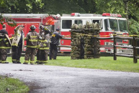 Police and firefighters stand near the site of a small plane crash in the town of Harrison, Westchester County, New York