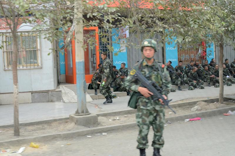 In this June 27, 2013 photo, an armed police officer stands guard in Lukqun township, Xinjiang, China. Violent incidents have spread over the past week in a tense minority region of western China, just days before the fourth anniversary of a bloody clash between minority Uighurs and the ethnic Han majority that left almost 200 people dead and resulted in a major security clampdown. (AP Photo/Kyodo News) JAPAN OUT, MANDATORY CREDIT