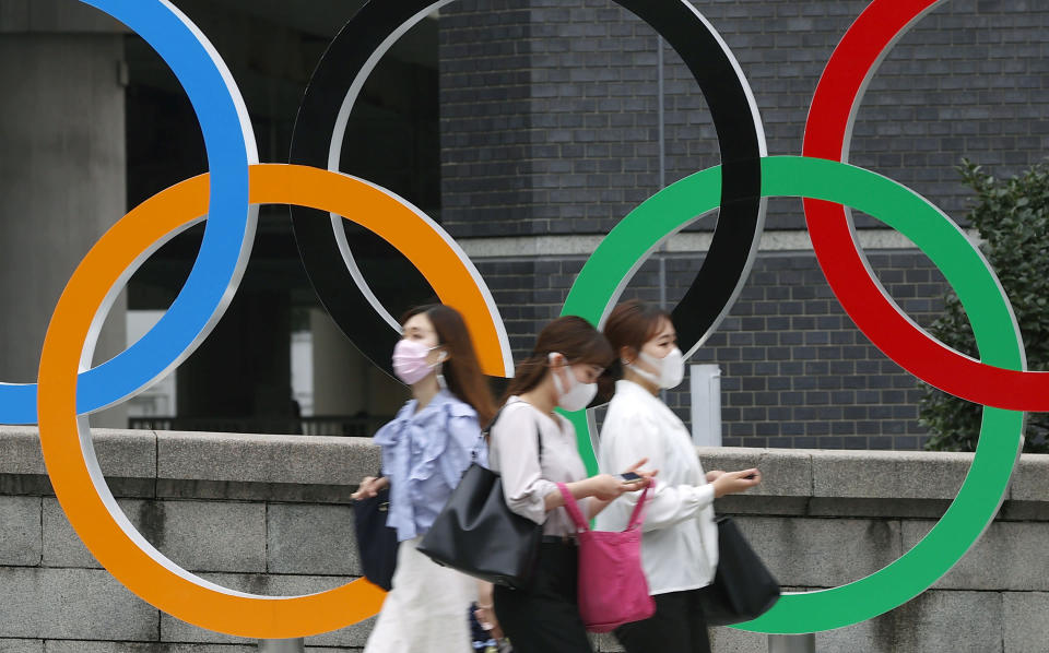 People wearing face masks walk past the Olympics Rings statue in Tokyo, Thursday, July 8, 2021. Japan is set to place Tokyo under a state of emergency starting next week and lasting through the Olympics, with COVID-19 cases surging and feared to multiply during the Games. (Shinji Kita/Kyodo News via AP)