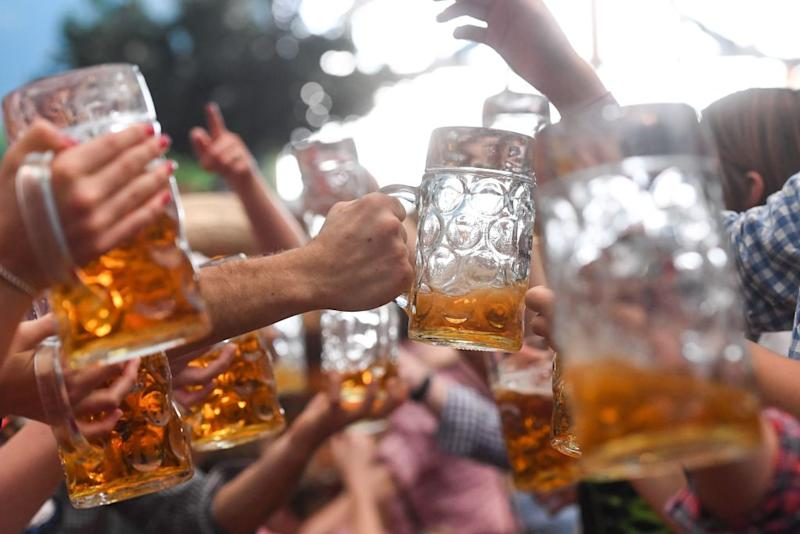 Visitors of the Oktoberfest beer festival clink their beer glasses on September 24, 2017 at the Theresienwiese fair grounds in Munich, southern Germany.