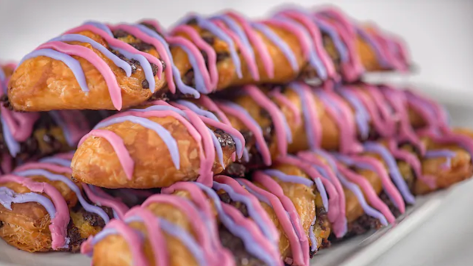 """<p>Fashioned after the Cheshire Cat from <em>Alice in Wonderland</em>, Cheshire Cat Tails are chocolate Danish twists with a whole bunch of colored icing that can be found at <a href=""""https://disneyworld.disney.go.com/dining/magic-kingdom/cheshire-cafe/"""" rel=""""nofollow noopener"""" target=""""_blank"""" data-ylk=""""slk:Cheshire Cafe"""" class=""""link rapid-noclick-resp"""">Cheshire Cafe</a>. </p>"""