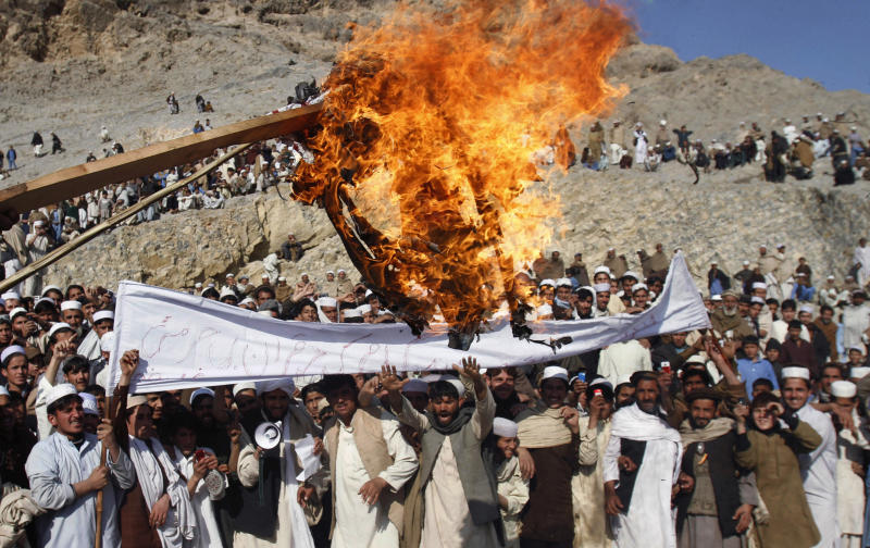 FILE - In this Feb. 24, 2012 file photo, Afghans burn an effigy representing U.S. President Barack Obama during an anti-U.S. protest in Ghani Khail, east of Kabul, Afghanistan over the burning of Qurans at a U.S. military base. Two U.S. troops were gunned down by an Afghan soldier and his accomplice Thursday, March 1, 2012, the latest of six American service members killed by their Afghan partners since the burning of Muslim holy books last week sent anti-Americanism soaring in a nation that has long distrusted foreigners. (AP Photo/Rahmat Gul, File)