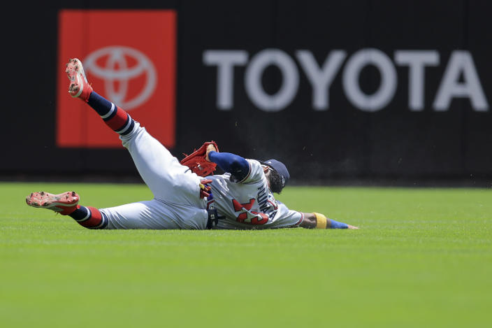Atlanta Braves' Ronald Acuna Jr. slides to make a catch for an out on a ball hit by Cincinnati Reds' Jonathan India during the first inning of a baseball game in Cincinnati, Sunday, June 27, 2021. (AP Photo/Aaron Doster)