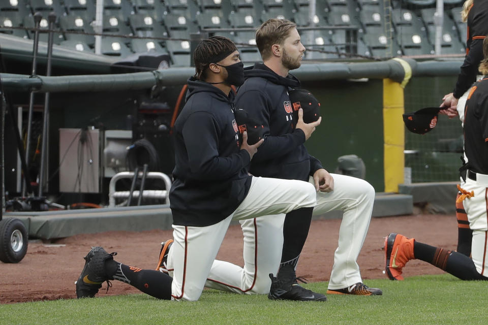 San Francisco Giants' Jaylin Davis, left, and Austin Slater kneel with others during the national anthem before an exhibition baseball game against the Oakland Athletics in San Francisco, Tuesday, July 21, 2020. (AP Photo/Jeff Chiu)