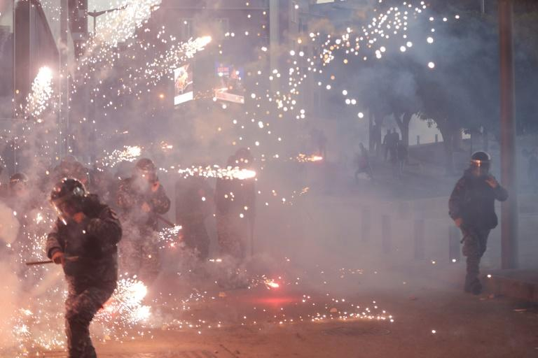 Lebanese counter-protesters threw firecrackers at riot police in central Beirut (AFP Photo/ANWAR AMRO)