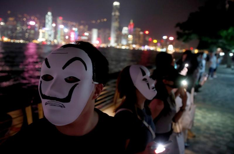 People wearing masks form a human chain during an anti-government protest in Hong Kong
