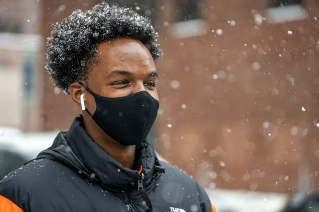 A man wearing a mask and earbuds walks along Bank Street during heavy snowfall on Feb. 19, 2021.