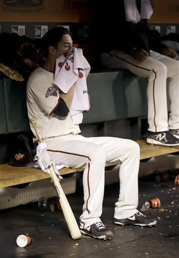 San Francisco Giants pitcher Tim Lincecum wipes his face in the dugout during the second inning of a baseball game against the Colorado Rockies in San Francisco, Tuesday, April 9, 2013. (AP Photo/Jeff Chiu)