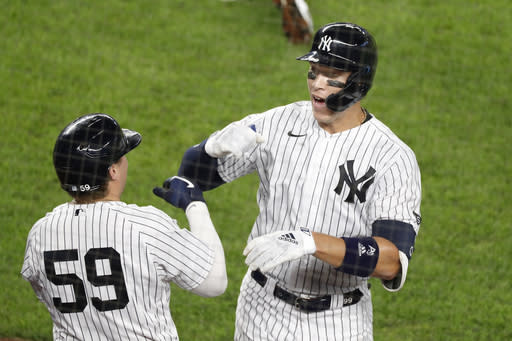 New York Yankees Aaron Judge, right, celebrates with the Yankees Luke Voit (59) after hitting a solo home run during the fifth inning of a baseball game against the Atlanta Braves, Tuesday, Aug. 11, 2020, in New York. (AP Photo/Kathy Willens)