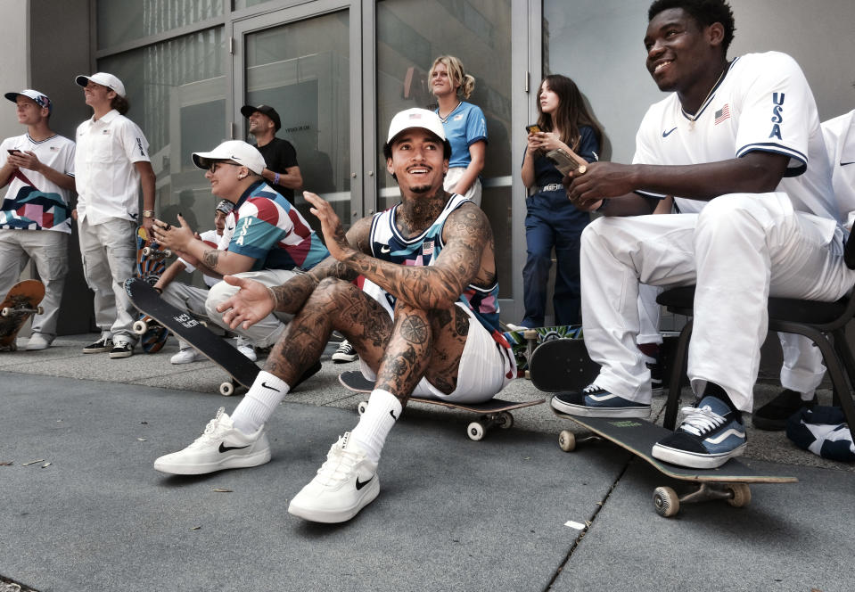 Nyjah Huston, center, laughs with teammate Zion Wright, right, before they are introduced with the rest of their team at a news conference in downtown Los Angeles on Monday, June 21, 2021. Huston and the rest of the first U.S. Olympic skateboarding team was introduced in Southern California on Monday where the sport was invented roughly 70 years ago. Skateboarding is an Olympic sport for the first time in Tokyo, and the Americans are expected to be a strong team. (AP Photo/Richard Vogel)