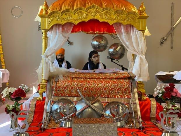 Ravjot Singh, left, and Gurpreet Kaur, right, read from the Guru Grath Sahib, the Sikh holy book, in Whitehorse over the weekend.  (Chris MacIntyre/CBC  - image credit)