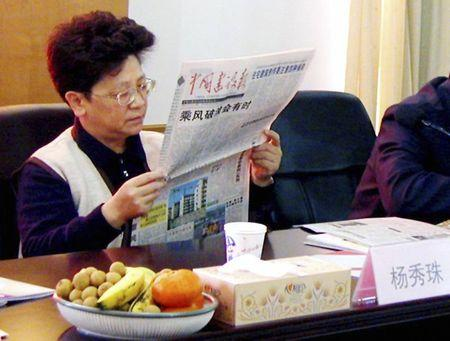 Yang Xiuzhu reads a newspaper during a meeting in Wenzhou