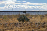 Newly erected border wall separating Mexico and the United States, cuts through through the Sonoran Desert just west of the San Bernardino National Wildlife Refuge, Wednesday, Dec. 9, 2020, in Douglas, Ariz. Construction of the border wall, mostly in government owned wildlife refuges and Indigenous territory, has led to environmental damage and the scarring of unique desert and mountain landscapes that conservationists fear could be irreversible. (AP Photo/Matt York)